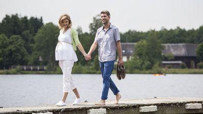 Schwangere geht mit Mann am See spazieren