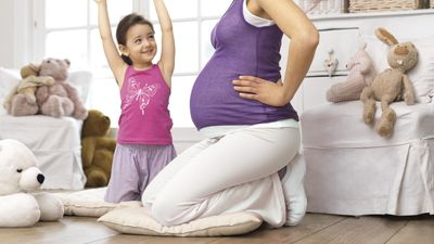 Schwangere hält sich den unteren Rücken