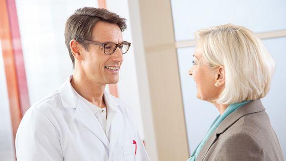 Arzt empfängt Patientin in der Praxis