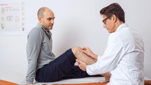 Arzt therapiert Knie eines Patienten