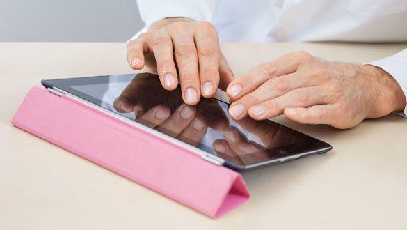 Hände bedienen ein Tablet