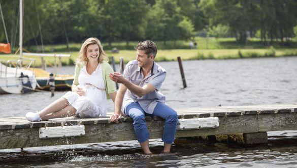 Schwangere Frau sitzt mit Mann am Wasser