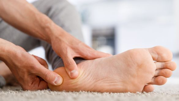 Man massaging his foot due to lower heel spur