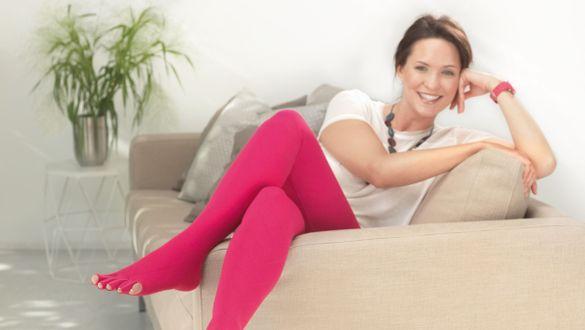 Frau entspannt mit Flachstrickversorgung auf dem Sofa