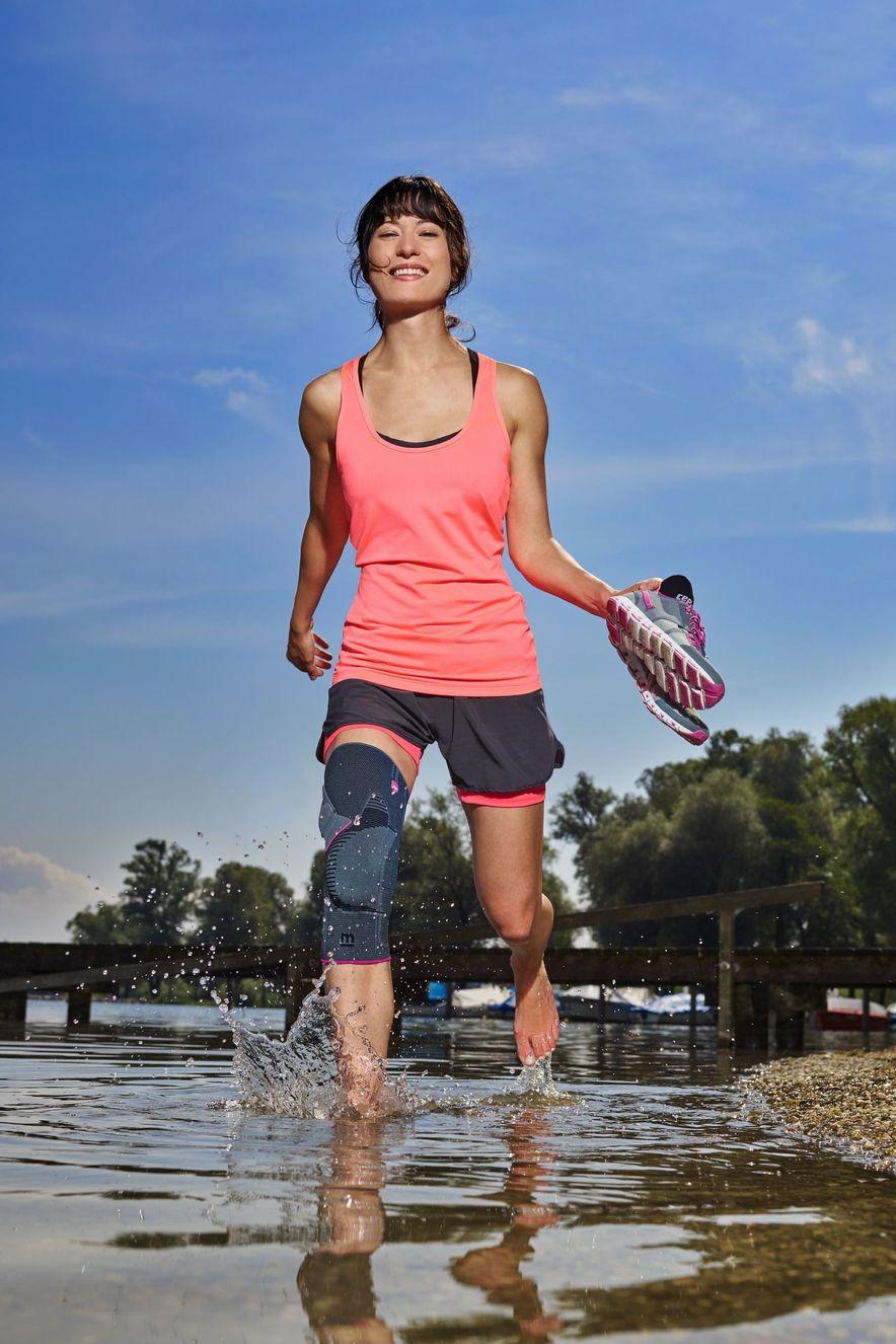 Frau trägt Genumedi PT Knieorthese am See