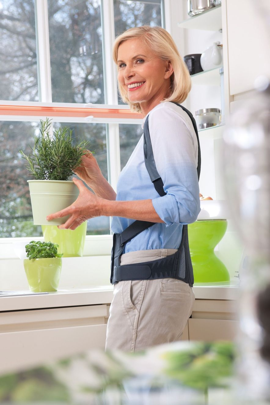 Frau steht in der Küche und trägt die Spinomed Rückenorthese