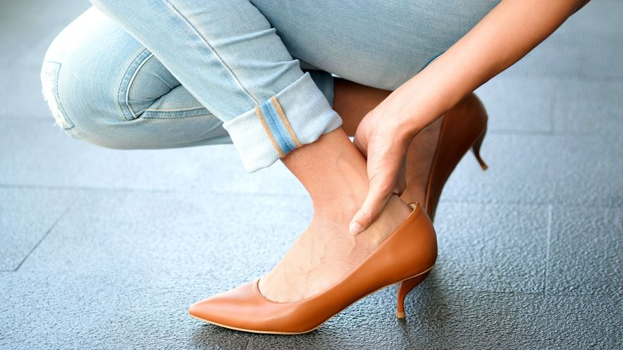 Woman touches achilles tendon insertion due to pain from rear heel spur